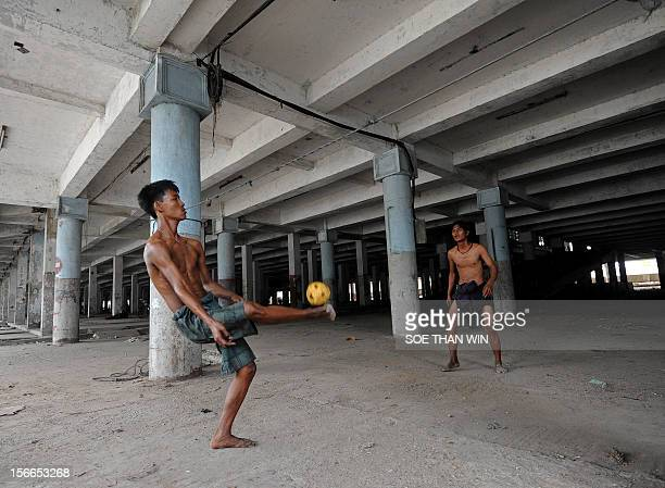Myanmar men play a game of separk takraw at an old building in Yangon on November 18 2012 The game which is played like volleyball with a rattan ball...