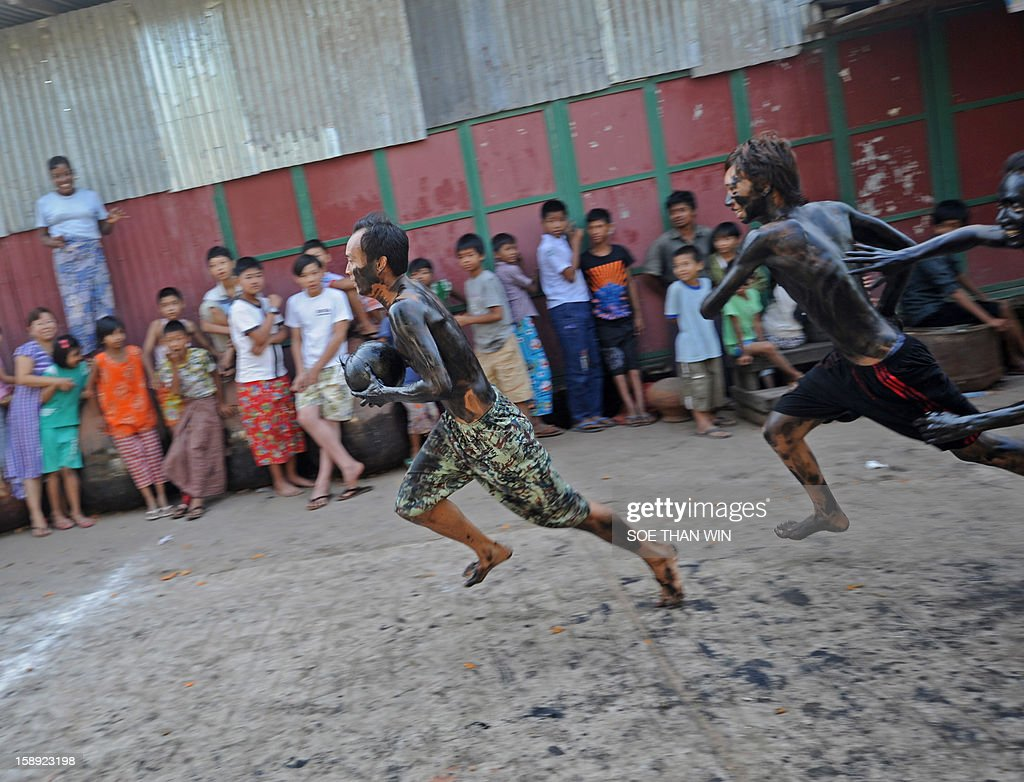 Myanmar men smeared with used car oil play a ball game with a coconut as they celebrate the 65th anniversary of Myanmar's independence, in Yangon on January 4, 2013. Myanmar, formerly known as Burma, gained independence from Britain on January 4, 1948. AFP PHOTO / Soe Than WIN