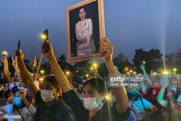 Myanmar migrant living in Thailand holds a portrait of detained civilian leader Aung San Suu Kyi while she and other hold up their mobile phone...