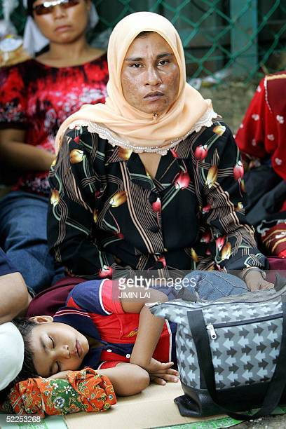 Myanmar migrant Morani and her fouryearold daughter sit camped out for the seventh day in a row outside the UNHCR office in Kuala Lumpur 28 February...