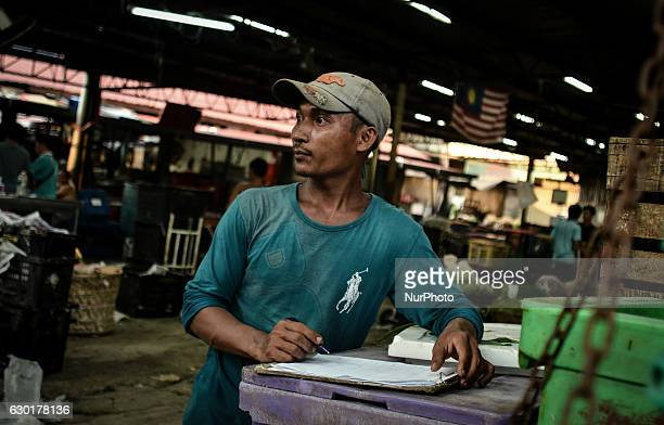 Myanmar migrant worker seen as he prepares a trading documents at a local market place located in the heart of Bukit Mertajam town on December 17,...