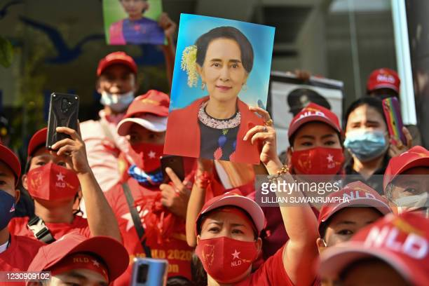 Myanmar migrants hold up portraits of Aung San Suu Kyi as they take part in a demonstration outside the Myanmar embassy in Bangkok on February 1...