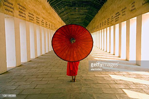 Myanmar: Monk with Red Parasol in Temple