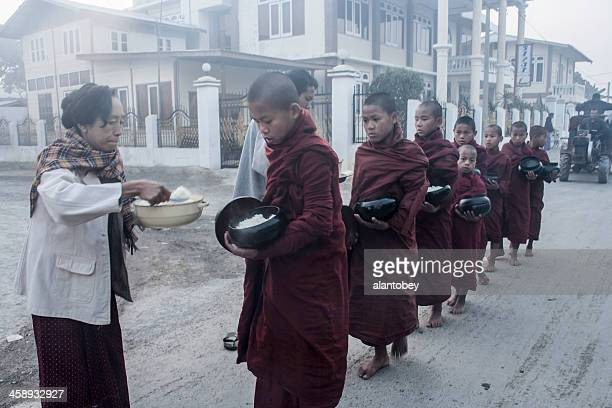 myanmar: monks receiving offering of rice - theravada stock pictures, royalty-free photos & images