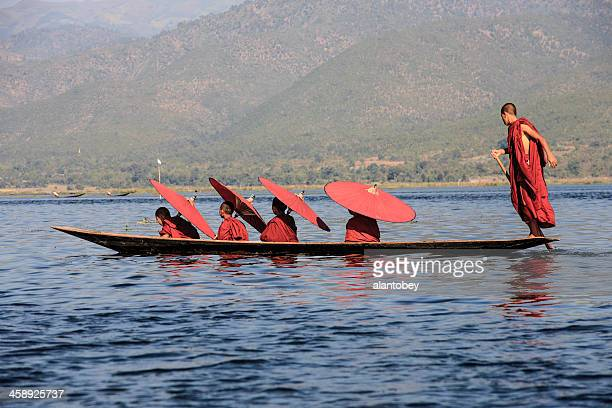 myanmar: monks with parasols crossing inle lake by boat - myanmar culture stock photos and pictures