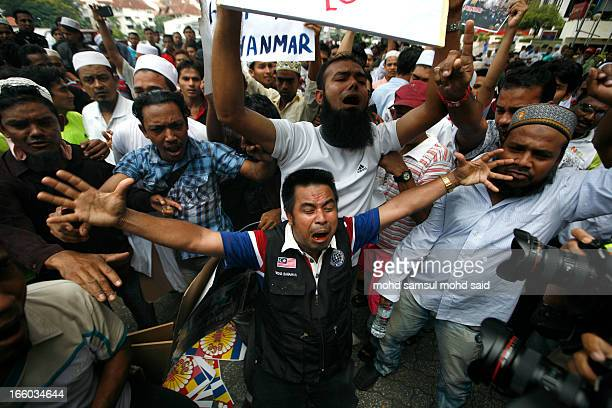 Myanmar Muslims living in Malaysia show the playcard against the killing of Muslims in Myanmar during a protest in Kuala Lumpur March 25, 2013....