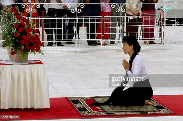 YANGON Myanmar Myanmar democracy icon Aung San Suu Kyi joins her hands before the mausoleum of her father independence hero Gen Aung San in Yangon on...