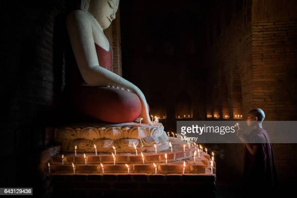 Myanmar Novice Monk praying in front of illuminated Buddha Statue