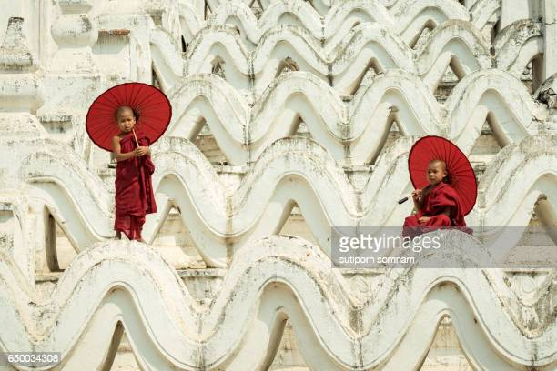 Myanmar Novice monks are playing on the white pagoda
