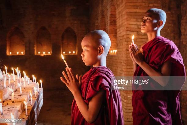 myanmar novice monks praying at buddha statue - religious symbol stock pictures, royalty-free photos & images
