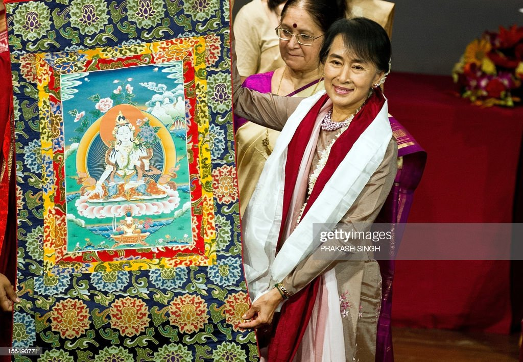 Myanmar opposition leader and National League for Democracy Chairperson Aung San Suu Kyi poses with a thangka painting presented to her as a gift during her visit to Lady Sri Ram College in New Delhi on November 16, 2012. Suu Kyi is in India for a seven day visit. AFP PHOTO/ Prakash SINGH