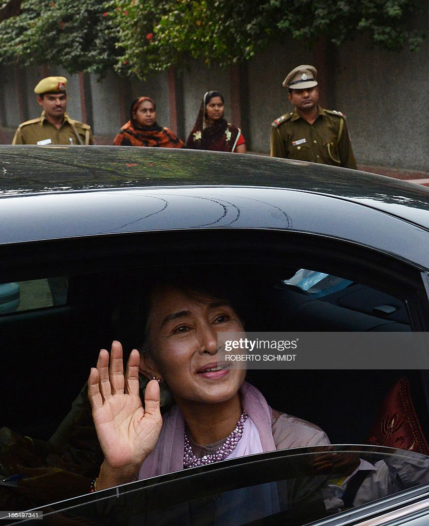 Myanmar opposition leader and National League for Democracy Chairperson Aung San Suu Kyi waves from the window of a car as she leaves a function at a school in New Delhi on November 16, 2012. The Nobel laureate, on a visit to neighbouring India and who is now a member of parliament after dramatic changes overseen by a quasi-civilian regime that took power last year, was released from military house arrest in 2010. AFP PHOTO/Roberto Schmidt