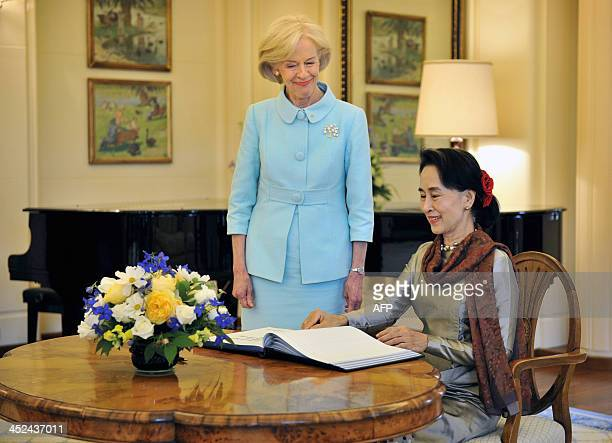 Myanmar opposition leader Aung San Suu Kyi signs the visitors book in front of Governor General Quentin Bryce at Government House in Canberra on...