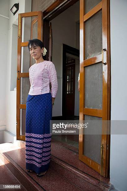 Myanmar opposition leader Aung San Suu Kyi stands at the door of her home saying goodbye to UNESCO officials February 10 2012 in Yangon Myanmar Suu...