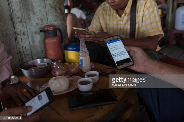 Myanmar people gather for refreshement at a teashop in Yangon on August 31 2018 many hangout to chat and browse facebook with their mobile phone...