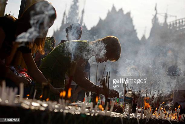 Myanmar people light candles at a pagoda during the Full Moon Festival in Yangon on October 30 2012 AFP PHOTO / Ye Aung Thu