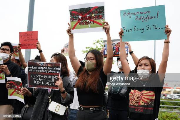 Myanmar people residing in Japan shouts their slogan holding signs that read 'This national team is not representing our citizens' and 'We don't...