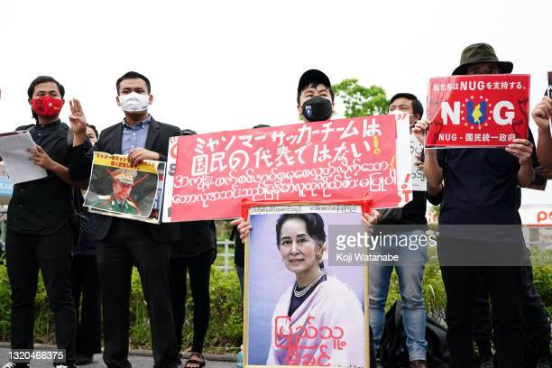 Myanmar people residing in Japan shouts their slogan holding the sign that read 'This national team is not representing our citizens' and a portrait...