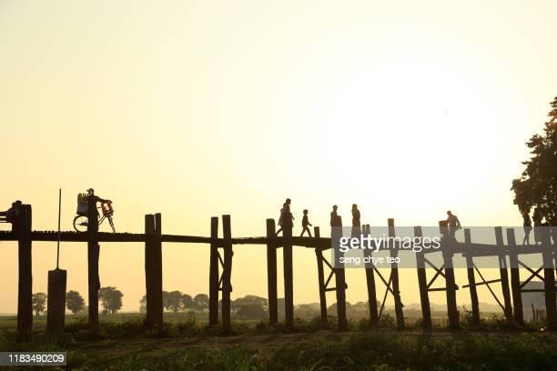myanmar people walking across u bein bridge, mandalay, myanmar - teak wood material stock pictures, royalty-free photos & images