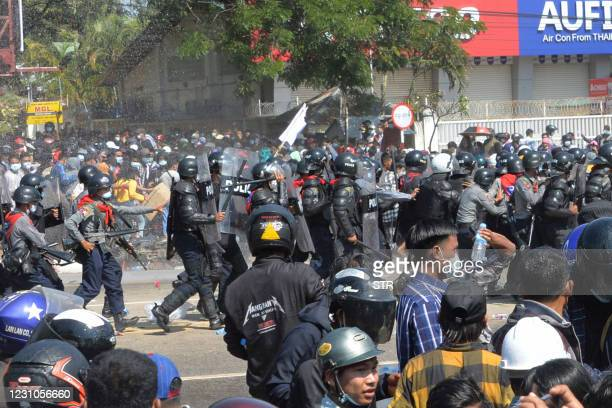 Myanmar police armed with automatic rifles move in on protesters as they continue to demonstrate against the February 1 military coup in the capital...