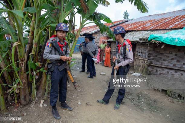 Myanmar police escort journalists during a government organized visit to Rohingya Muslims confined at Thet Kae Pyin camp in Rakhine state as they...
