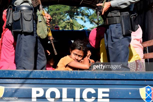 Myanmar police escort Rohingya Muslims back to their camp in Sittwe Rakhine state on November 30 2018 Nearly 100 Rohingya Muslims were forced back to...