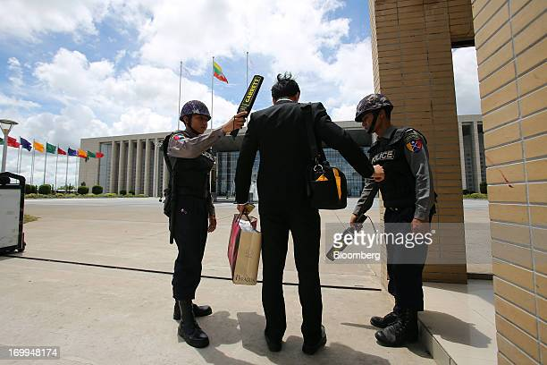 Myanmar Police Force officers wave metal detector scanners over a man at the entrance to the Myanmar International Convention Center ahead of the...
