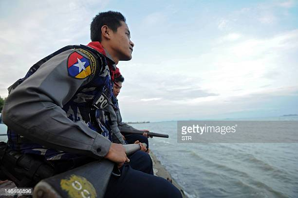 Myanmar police stand guard on a river bank in Sittwe on June 17, 2012. Myanmar pledged to hunt down those responsible for the deaths of 50 people in...