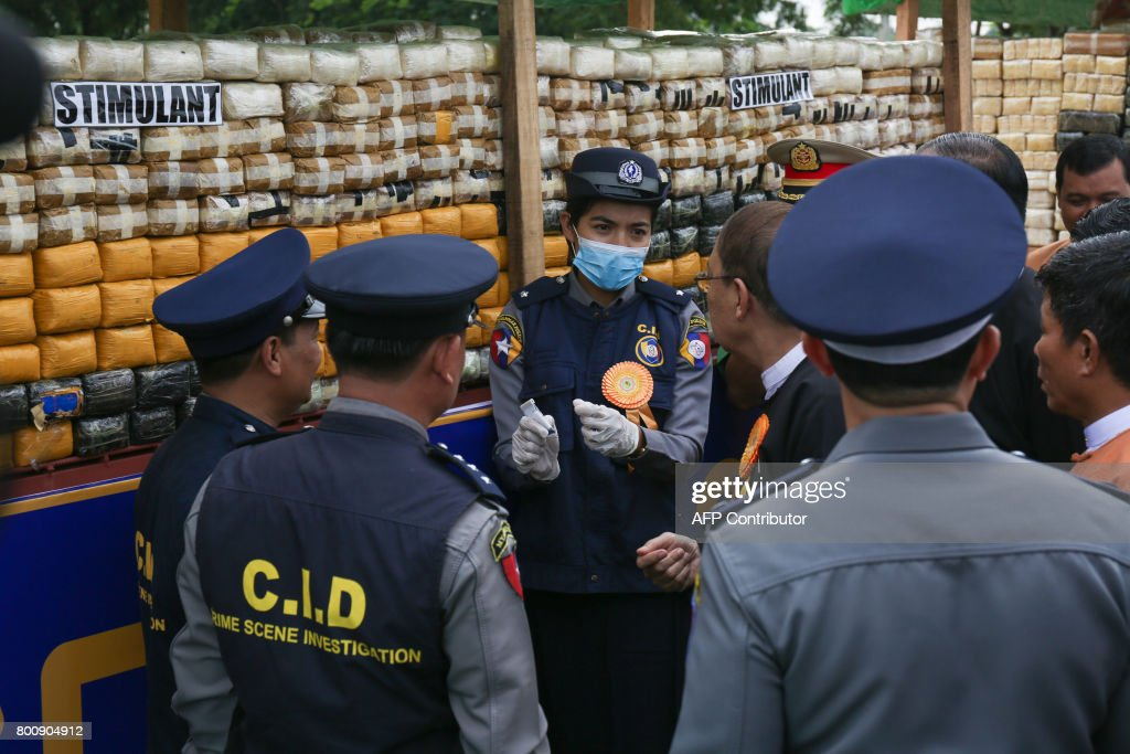 Myanmar police test a sample of confiscated drugs before