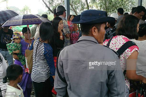 A Myanmar policeman secures a river jetty in Sittwe as crowds of teachers and civil servants who are fleeing from Maungdaw arrive as government...
