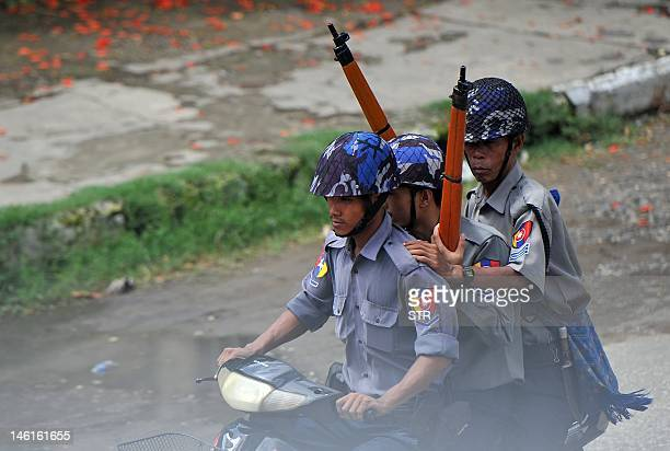 Myanmar policemen patrol with rifles on the streets of Sittwe, capital of the western state of Rakhine, on June 11, 2012. Security forces tried to...
