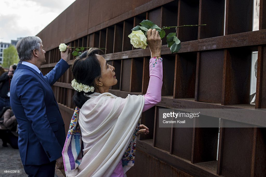 Myanmar pro-democracy leader Aung San Suu Kyi (R) and Berlin's Major Klaus Wowereit place flowers on a memorial for victims of the Berlin wall during a visit to the Berlin Wall Memorial on April 12, 2014 in Berlin, Germany. Myanmar's opposition leader and Nobel laureate Aung San Suu Kyi visits Germany for some days.