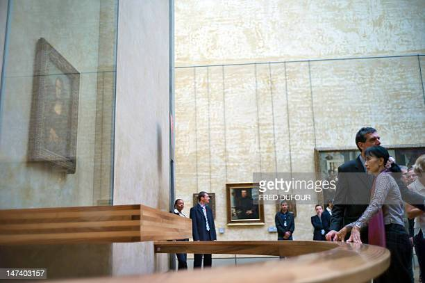 Myanmar prodemocracy leader Aung San Suu Kyi looks at a portrait of Mona Lisa painted by Leonardo da Vinci during a visit at the Louvre Museum in...