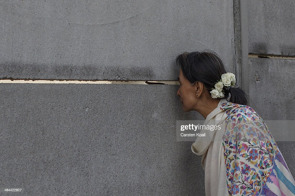 Myanmar pro-democracy leader Aung San Suu Kyi peeks through a crack in the back wall during a visit to the Berlin Wall Memorial on April 12, 2014 in Berlin, Germany. Myanmar's opposition leader and Nobel laureate Aung San Suu Kyi visits Germany for some days.