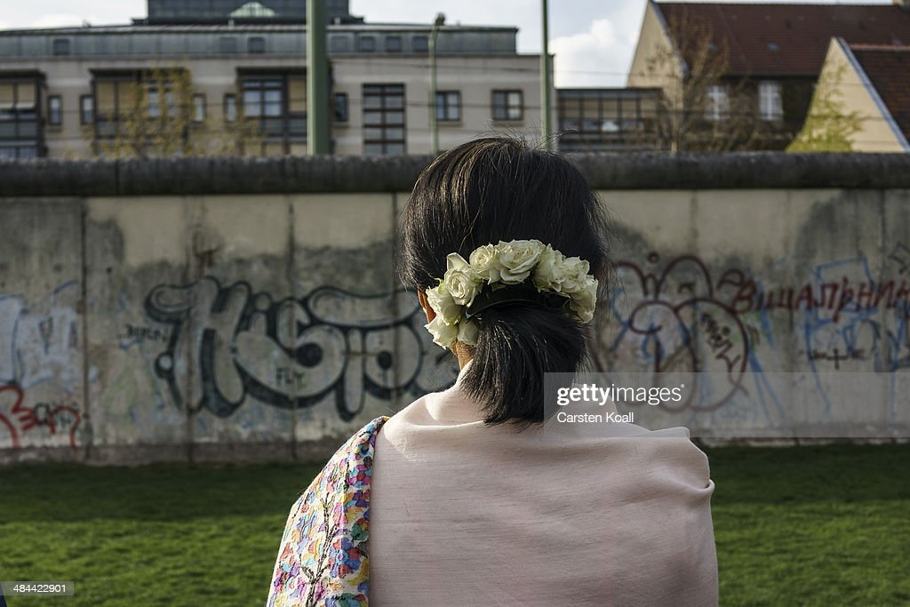 Myanmar pro-democracy leader Aung San Suu Kyi stays in front of the wall backside during a visit to the Berlin Wall Memorial on April 12, 2014 in Berlin, Germany. Myanmar's opposition leader and Nobel laureate Aung San Suu Kyi visits Germany for some days.