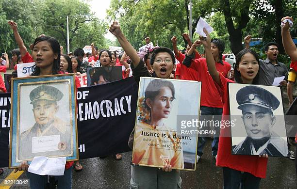 Myanmar protestors shout anti-military slogans as they display a portrait of Myanmar's opposition leader Aung San Suu Kyi during a demonstration to...