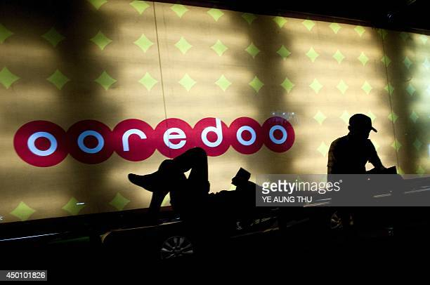 Myanmar residents wait at a bus stop in front of a billboard advertising telecoms firm Ooredoo in Yangon on June 5 2014 Radical Myanmar Buddhist...