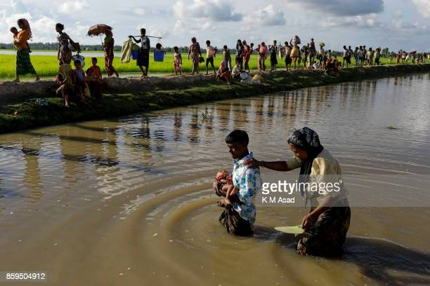 Myanmar Rohingya people walk in the paddy fields as they cross Bangladesh's border as they flee from Buchidong at Myanmar after crossing the Naf...