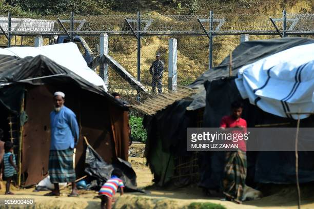 A Myanmar security personnel keeps watch along the MyanmarBangladesh border as Rohingya refugee stand outside their makeshifts shelters near Tombru...