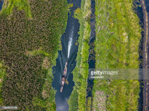 myanmar, shan state, nyaungshwe township, aerial view of rowboat passing floating gardens on inle lake - myanmar stock pictures, royalty-free photos & images