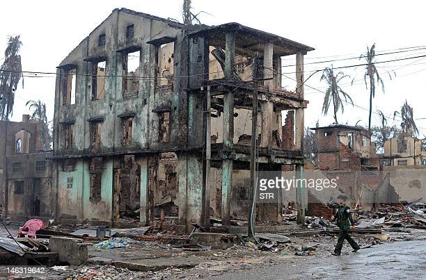 Myanmar soldier patrols past a partially destroyed building in Sittwe, capital of the western state of Rakhine on June 14, 2012. More than 30,000...