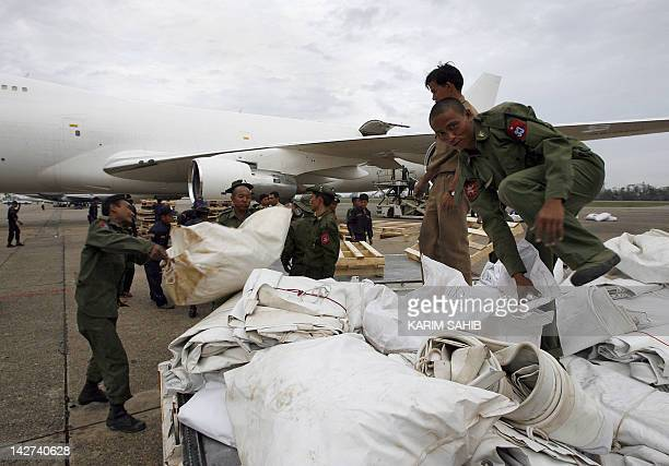Myanmar soldiers and 'Dubai Cares' personnel offload aid from Dubai at Yangon International Airport for victims of Cyclone Nargis on 12 May 2008 The...