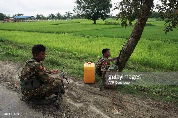 Myanmar soldiers man a check point in a rural road near Maungdaw on August 30 2017 Plumes of smoke billowed from several burning villages in the...