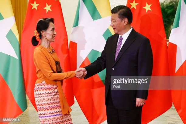 Myanmar State Counsellor Aung San Suu Kyi shakes hands with Chinese President Xi Jinping as they meet at the Great Hall of the People on May 16 2017...
