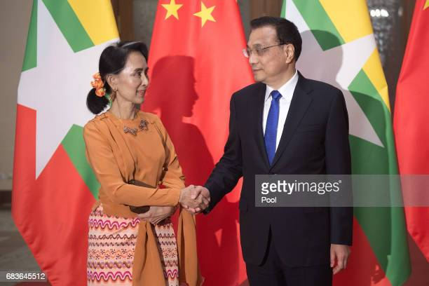 Myanmar State Counsellor Aung San Suu Kyi shakes hands with Chinese Premier Li Keqiang at the Great Halll of the People on May 16 2017 in Beijing...