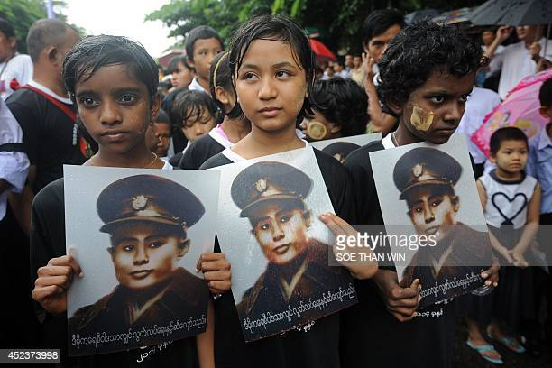Myanmar students hold portraits of General Aung San as they wait to pay their respects to mark Myanmar's 67th anniversary of Martyrs' Day in Yangon...