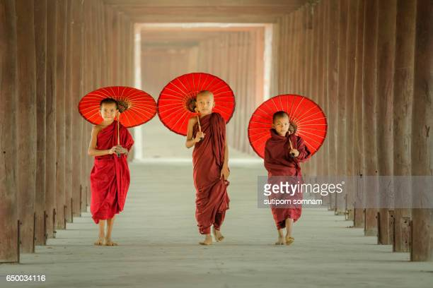 Myanmar The three novice walking on the pagoda and holding red umbrella