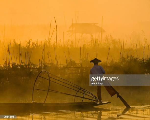 myanmar: traditional fisherman on inle lake, hazy dawn light - inle lake stock pictures, royalty-free photos & images