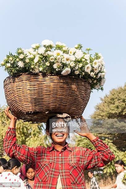 myanmar: woman carrying basket of flowers - myanmar culture stock pictures, royalty-free photos & images
