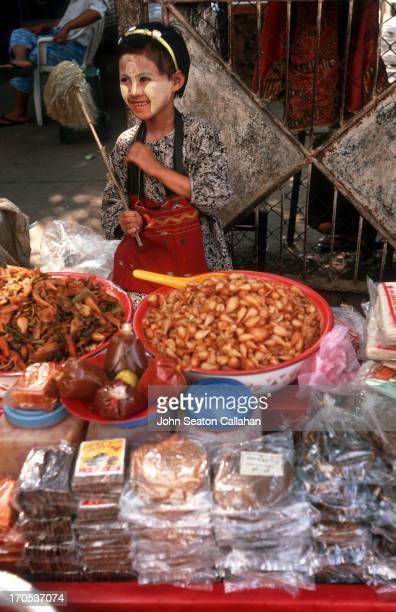 Myanmar, Yangon, young girl selling snacks outside the Shwedagon Pagoda.